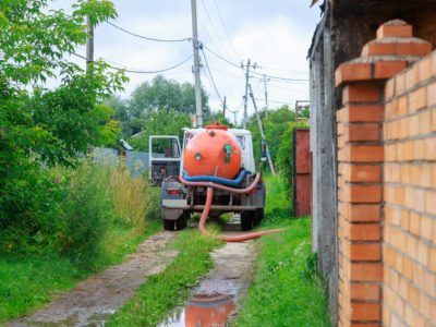 A Sewage truck working in village environment.