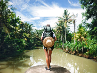 Woman with backpack standing on the edge near big tropical river and looking far away